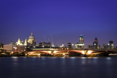 skyline of central london at night thames river flowing past st pauls and the city financial district photo