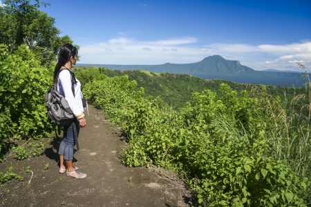 filipina girl looking at taal volcano crater lake from trail along rim near manila in the philippines photo
