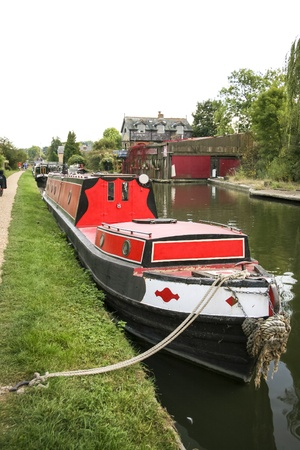 mooring: red narrowboat barge moored on the grand union canal inland waterway in berkhamsted hertfordshire uk Stock Photo