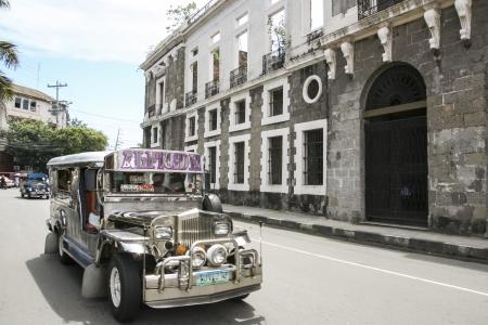 MANILA - 10. Juli: jeepney öffentlichen Verkehrsmitteln fahren vorbei an verlassenen Gebäude in intramuros am 10. Juli 2009 in Manila. Jeepneys sind die beliebtesten Mittel der öffentlichen Verkehrsmittel in den Philippinen. Standard-Bild - 20030187