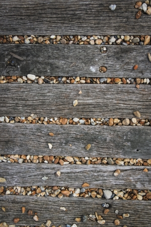 brighton beach: pebbles covering old wooden  pathway on brighton beach sussex england Stock Photo