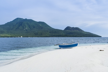 outrigger: traditional banka outrigger canoe on white beach camiguin island, mindanao in the philippines, with volcano in the background