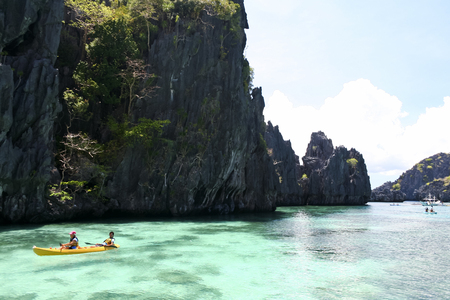 costal: El Nido, Palawan in the Philippines - May 19 2007: tourists kayaking through the costal karst lagoons - EL Nido is ranked as one of the best travel destinations in the world winning many travel awards