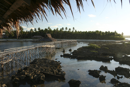 elevated walkway: view back to tropical siargao island from cloud 9 surf break across the elevated walkway used to cross the reef