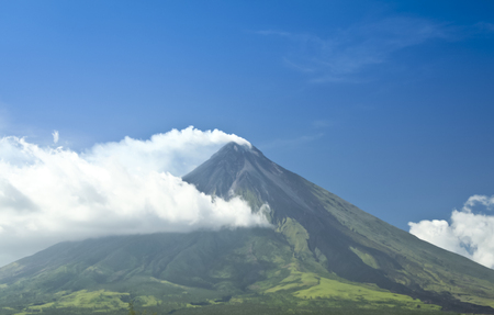 mt mayon volcano smoking against a blue sky, with dark trail of lava marking the sides from a recent eruption