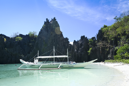 nido: El Nido, Philippines - May 18, 2007: banka outrigger tour boat in hidden lagoon where tourists swim . El Nido is one of the top tourist destinations in the world. Editorial