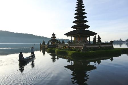 People on boat approcahing Pura Ulun Danu water temple on lake brataan near bedugal, bali, indonesia