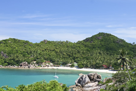 white sailboat anchored in beautiful crystal bay surrounded by jugle clad hills near lamai on ko samui island in the gulf of thailand Stock Photo