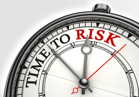 risk time concept clock closeup on white background with red and black words photo