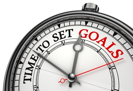 goals: time to set goals concept clock closeup isolated on white background with red and black words