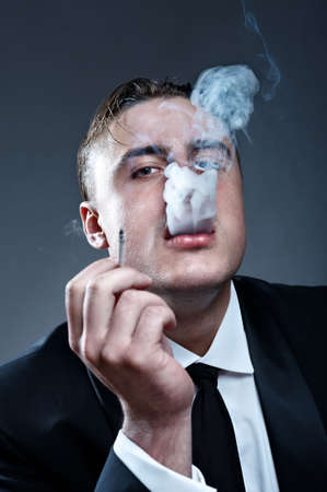 Closeup portrait of smoking handsone young man in suit photo