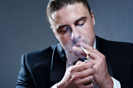 smoking issues: Closeup portrait of smoking handsone young man in suit