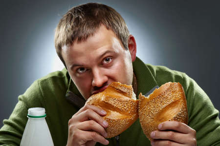 Hungry man with mouth full of bread Stock Photo