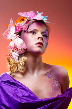 Colorful fashion portrait of attractive young beauty with butterflies in hairs