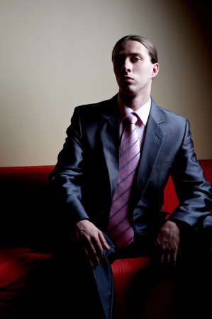 contrasty: Contrasty portrait of handsome serious man on sofa
