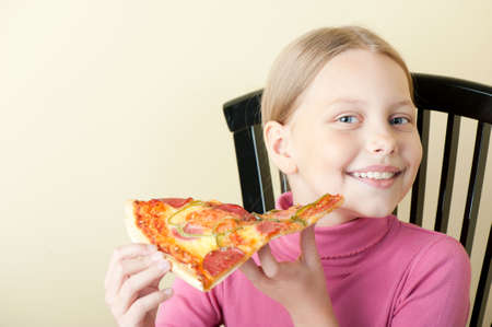 Cheerful little girl with delicious pizza