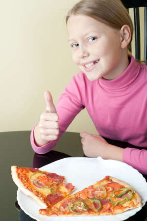 Cheerful little girl with delicious pizza photo