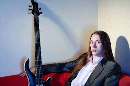 Portrait of young handsome musician with bass guitar photo