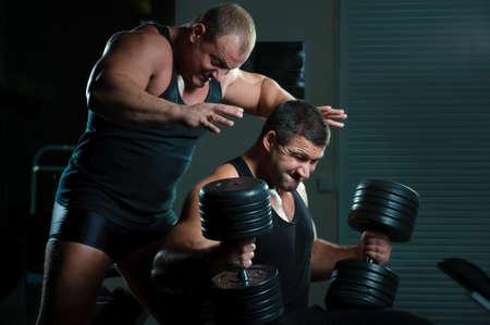 Two bodybuilders training in gym