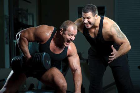 levantamiento de pesas: Dos los culturistas entrenamiento en gimnasio  Foto de archivo