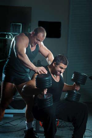 Bodybuilders training hard in gym