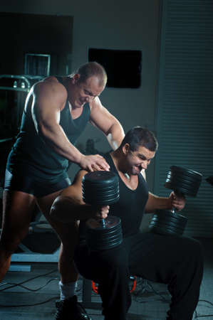 Bodybuilders training hard in gym photo