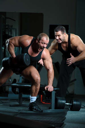 gym: Bodybuilders training hard in gym