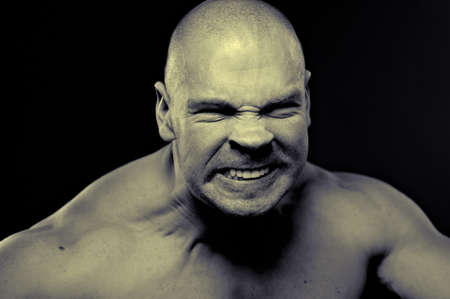 Emotional portrait of muscular aggressive man photo