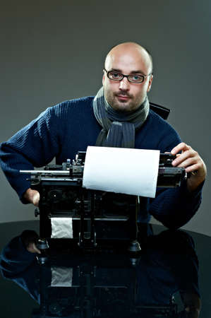 Old fashioned bald writer in glasses writing book on a vintage typewriter Standard-Bild