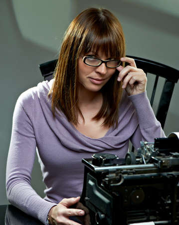 types of glasses: Beautiful young woman in glasses at a vintage typewriter