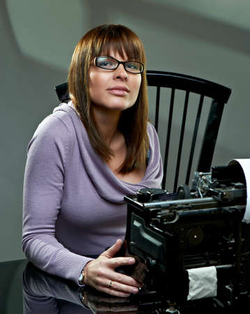 Beautiful young woman in glasses at a vintage typewriter photo