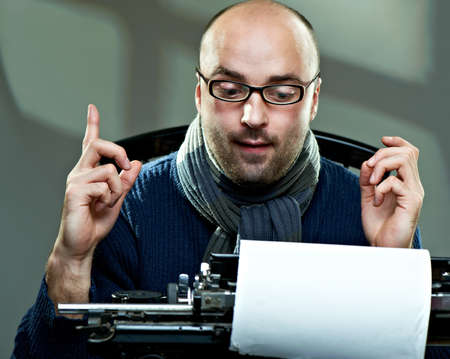 author: Old fashioned bald writer in glasses writing book on a vintage typewriter Stock Photo