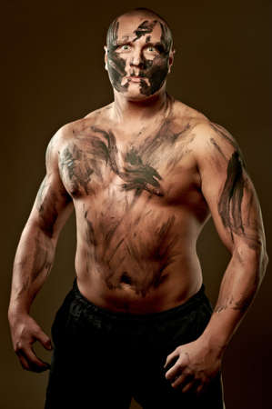 Emotional portrait of fighter. War paint on his face and body