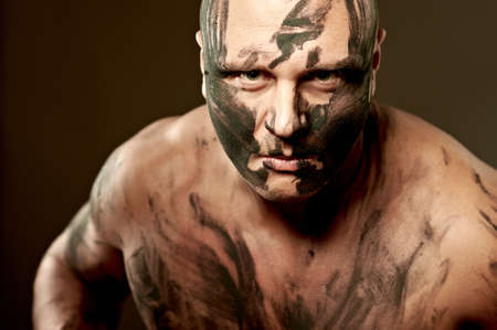 Emotional portrait of fighter. War paint on his face and body photo