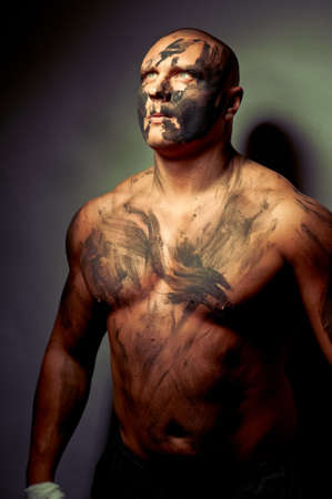 creative strength: Emotional portrait of fighter. War paint on his face and body