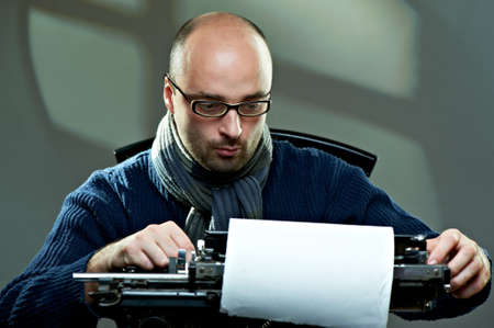 scripts: Old fashioned bald writer in glasses writing book on a vintage typewriter Stock Photo