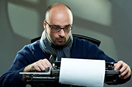 Ouderwetse kale schrijver in glazen schrijven boek over een vintage typewriter