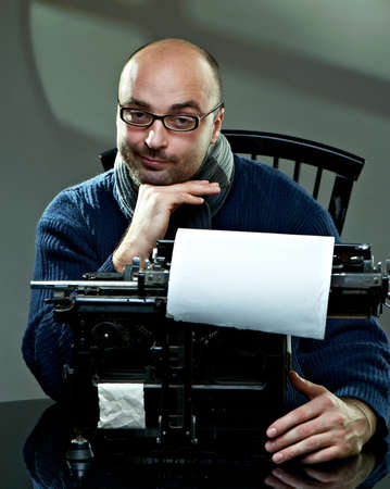 Old fashioned bald writer in glasses writing book on a vintage typewriter photo