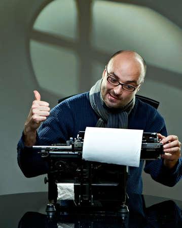 Old fashioned bald writer in glasses writing book on a vintage typewriter Zdjęcie Seryjne