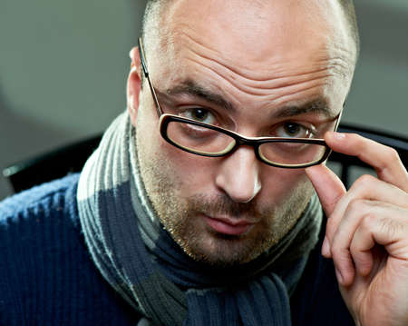 Portrait of a bald serious man in glasses