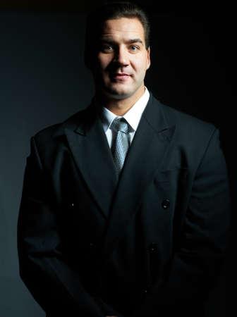 Dark portrait of handsome stylish young man in black suit, studio shot Stock Photo - 8489189