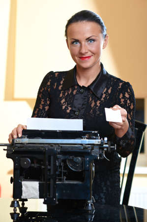 Young pretty woman sitting at a typewriter with white blank card in hand photo