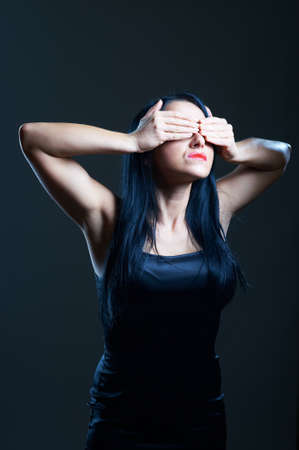 Portrait of young woman in darkness covering her eyes photo
