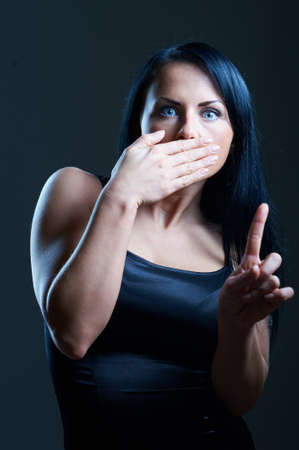 Don't Say a Word. Young woman in darkness, covering her mouth photo