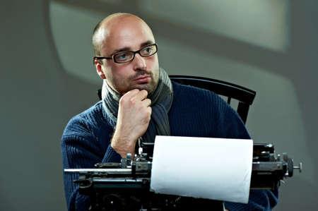 Serious bald man at a typewriter Stock Photo