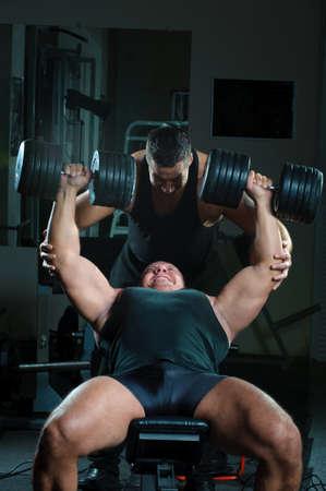levantando pesas: Dos muscullar fuerte mans cuerpo de entrenamiento en el gimnasio.