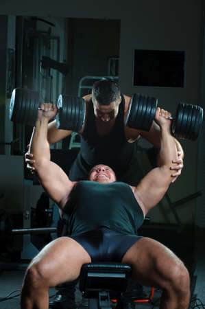 heavy lifting: Two strong muscullar mans training body in gym.