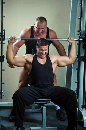 Two strong muscullar mans training body in gym.  photo