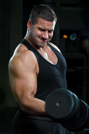 heavy lifting: Strong muscullar man training body in gym.