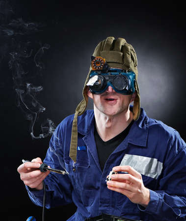 genius: Crazy funny genious with soldering iron Stock Photo